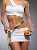 与评定的磁带和桔子的秀丽女性身体 免版税库存照片