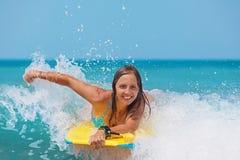 与识别不明飞机委员会的快乐的女孩游泳在海挥动 免版税库存图片