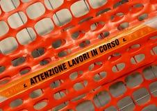 与词在CORSO的ATTENZIONE LAVORI的塑料橙色安全网 库存照片