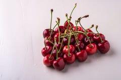 与词根的樱桃莓果在木白色背景和水下落 免版税图库摄影