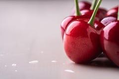 与词根的樱桃莓果在木白色背景和水下落 免版税库存照片