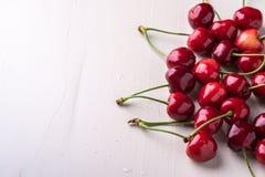 与词根的樱桃莓果在木白色背景和水下落 库存图片