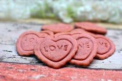 与词的桃红色心形的家庭焙制的情人节曲奇饼在他们爱 免版税库存照片