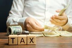 与词税和计数金钱的商人的木块 税的时间付款的概念 税率 征税/ 库存图片