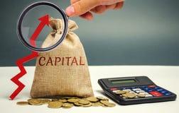 与词资本和一个箭头的金钱袋子 储积和增量的概念在金钱首都 在首都的增量 图库摄影