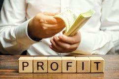 与词赢利和计数金钱的一个人的木块 公司的财务成果某一时段 免版税图库摄影