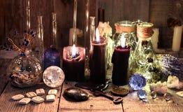 与诗歌、水晶、医治草本和礼节对象的黑蜡烛 库存照片