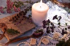 与诗歌、裂缝合拢草本、巫婆日志、白色蜡烛和发光的瓶的静物画在鞋带 库存图片