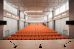 与话筒和计算机的抽象迷离讲台在会场里 橙色颜色 免版税库存照片