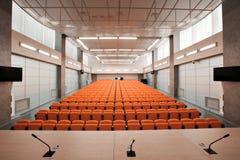 与话筒和计算机的讲台在会场里 橙色颜色 免版税库存照片