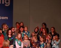与话筒的女童子军问希拉里・克林顿问题 免版税库存图片