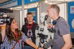 与话筒的妇女电视新闻工作者采访在他的developme旁边站立的工程师开发商机器人寄生虫 图库摄影