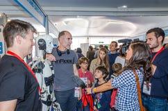 与话筒的妇女电视新闻工作者采访在他的developme旁边站立的工程师开发商机器人寄生虫 库存照片