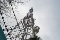 与话筒的电视塔反对多云天空 库存照片