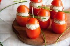 与说谎在一个棕色木板的鸡,大蒜和乳脂干酪面团的西红柿原料 免版税库存照片