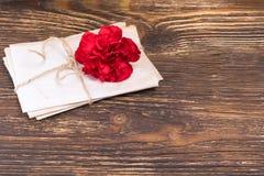 与说谎在木老桌上的一朵红色花的纸信件,安置图表在右边 库存照片