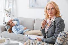 与说谎在沙发的客户的女性psychologyst疗期户内看照相机 免版税库存照片