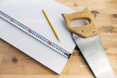 与说谎在白色盘区的锯、黄色铅笔和磁带统治者的木背景 库存图片