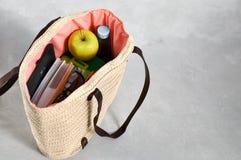 与课本和笔记本、饭盒和绿色苹果计算机,快餐和太阳镜的水的时髦的时兴的柳条袋子 图库摄影