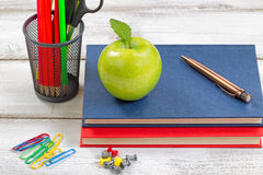 与课本的学校用品在白色桌面上 库存图片