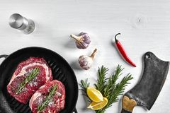 与调味料的未加工的水多的牛排在一个黑平底锅准备好烤在白色背景 顶视图 库存照片