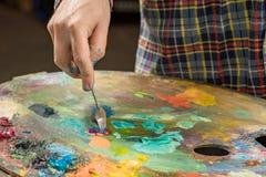 与调色刀的艺术绘画 艺术家的手 免版税库存图片
