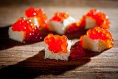 与谋生的红色鱼子酱在黑暗的背景 免版税库存照片