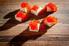 与谋生的红色鱼子酱在黑暗的背景 免版税图库摄影