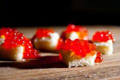 与谋生的红色鱼子酱在黑暗的背景 图库摄影