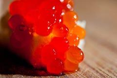 与谋生的红色鱼子酱在黑暗的背景 库存图片