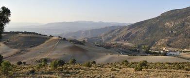 与谷物和山的被犁的领域的农舍在背景中 免版税库存图片