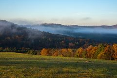 与谷雾的秋叶日出在Claremont,新罕布什尔 免版税库存图片