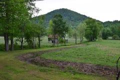 与谷仓和山的牧场地视图 免版税图库摄影