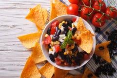 与豆和玉米片烤干酪辣味玉米片的墨西哥辣调味汁 水平的上面 免版税库存图片