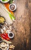 与豆腐、面条、香料、菜和调味汁的各种各样的亚洲烹调成份烹调在土气woode的鲜美素食主义者的 免版税库存照片