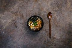 与豆腐和三文鱼的日本大酱汤在葡萄酒的一个黑碗上色了与一把木匙子的背景 顶视图 图库摄影