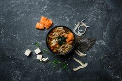 与豆腐和三文鱼的日本大酱汤在葡萄酒的一个黑碗上色了与成份的背景 顶视图 免版税库存图片