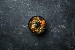 与豆腐和三文鱼的日本大酱汤在葡萄酒的一个黑碗上色了背景 垂直的看法从上面 库存图片