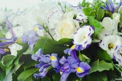 与豪华的叶子的美丽的蓝色虹膜花,白色八仙花属,精美奶油色玫瑰 夏天婚礼概念背景 免版税库存图片