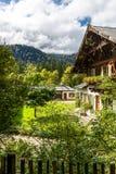 与豪华的绿色庭院的高山瑞士山中的牧人小屋 免版税库存照片