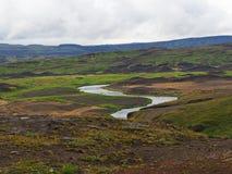 与豪华的草熔岩小山的绿河谷和青苔和moun 免版税库存照片