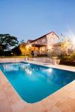 与豪宅的现代游泳池在与光的晚上 库存图片