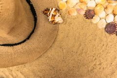 与贝壳、妇女的海滩帽子和太阳镜的暑假概念在沙子背景   免版税库存图片