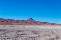 与贫瘠沙漠风景的背景在自然保护的Edoardo Avaroa玻利维亚人安地斯, 免版税库存图片