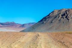与贫瘠沙漠风景的背景在自然保护的Edoardo Avaroa玻利维亚人安地斯, 免版税图库摄影