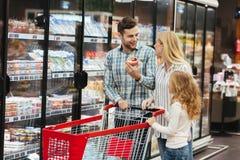 与购物车的愉快的家庭在超级市场 库存照片