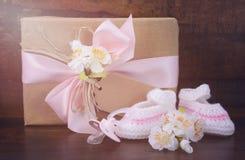 与赃物的婴儿送礼会礼物在黑暗的木头 免版税库存图片