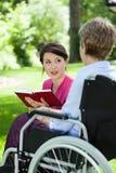 与资深妇女的女性照料者阅读书 免版税库存图片