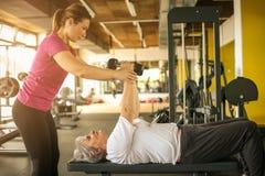 与资深妇女的教练员运作的锻炼健身房的 库存图片