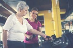 与资深妇女的教练员运作的锻炼健身房的 库存照片